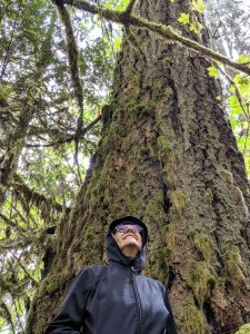 Lyn Cikara in front of a beautiful Douglas Fir tree